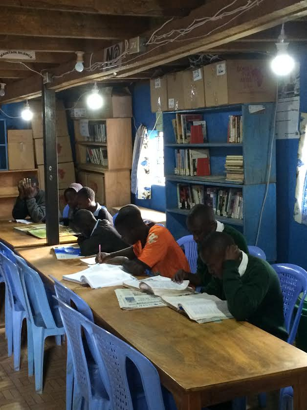 SHOFCO Community Members reading by new light