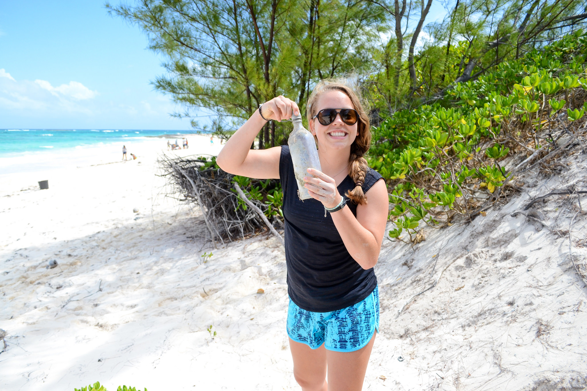 Lily picks up trash during a beach clean-up on Eleuthera